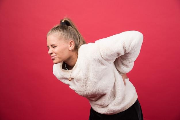 Uma jovem em pé e tocando a parte inferior das costas, sentindo sensações dolorosas. foto de alta qualidade