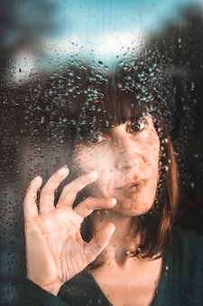 Uma jovem em quarentena da pandemia de covid-19 na janela em um dia chuvoso