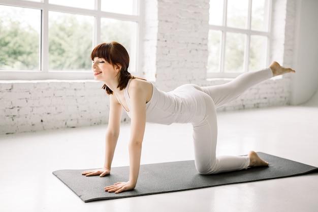 Uma jovem em roupas esportivas brancas faz exercícios de aptidão física, hidrante para as pernas