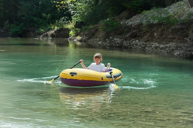 Uma jovem em um barco inflável nas molas.