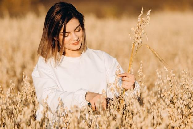 Uma jovem em um campo de aveia segura um monte de espigas de milho maduras.
