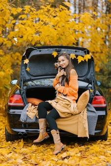 Uma jovem em um carro no porta-malas no contexto da floresta de outono