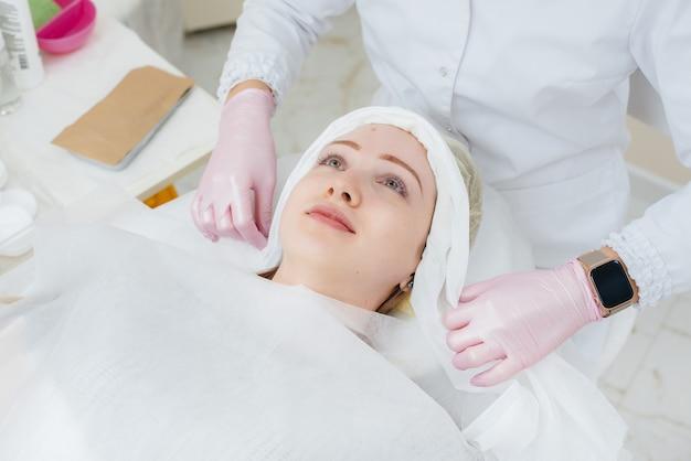Uma jovem em um consultório de cosmetologia está passando por procedimentos de rejuvenescimento da pele facial. cosmetologia.