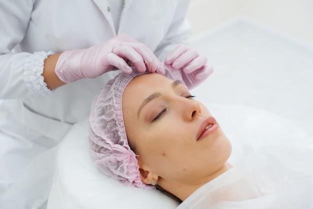 Uma jovem em um consultório de cosmetologia está passando por procedimentos de rejuvenescimento da pele facial