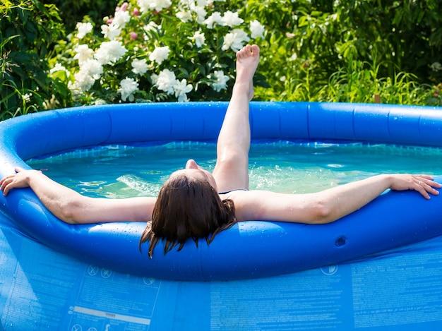 Uma jovem em um dia quente de verão relaxa na piscina em seu site