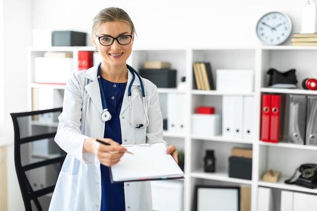 Uma jovem em um jaleco branco está de pé perto de uma mesa em seu escritório e segurando um tablet e uma caneta.