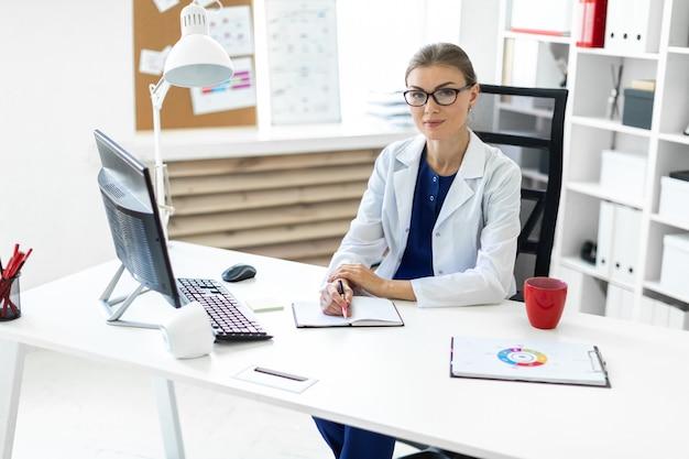 Uma jovem em um manto branco senta-se nas mesas no escritório e detém uma caneta na mão. um estetoscópio está pendurado no pescoço dela.