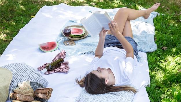 Uma jovem em um piquenique lendo um livro