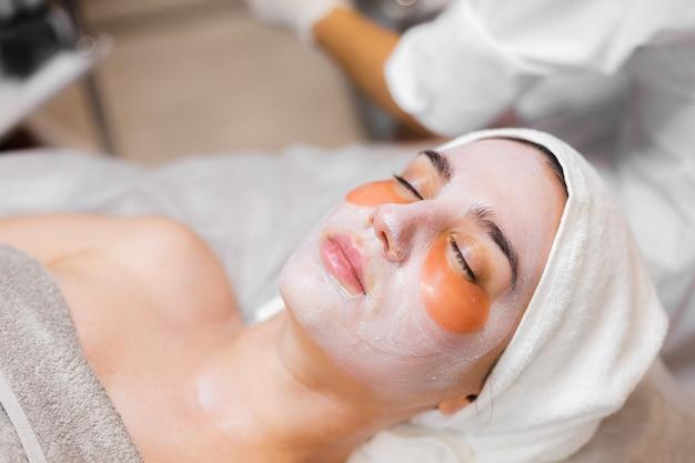 Uma jovem em um salão de beleza em uma sala de cosmetologia está deitada em uma cama e relaxa com uma máscara no rosto e manchas sob os olhos