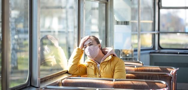 Uma jovem em um transporte público vazio durante a pandemia.