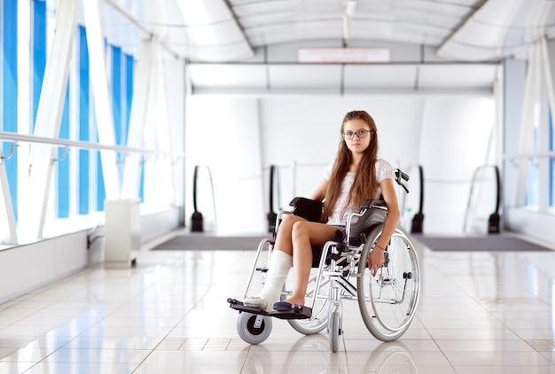 Uma jovem em uma cadeira de rodas está de pé no corredor do hospital.