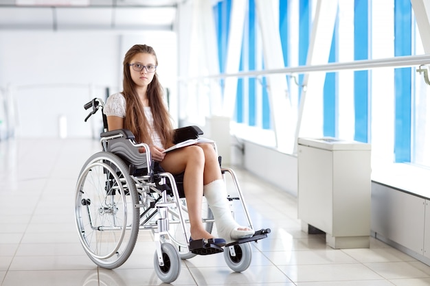 Uma jovem em uma cadeira de rodas está lendo um livro. paciente em uma cadeira de rodas no corredor do hospital.