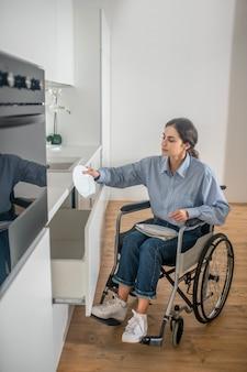 Uma jovem em uma cadeira de rodas fazendo algumas tarefas domésticas e parecendo envolvida