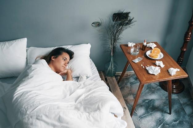 Uma jovem em uma cama doente olha seus remédios com o canto do olho