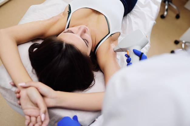 Uma jovem em uma clínica de cosmetologia moderna sobre o procedimento de depilação a laser na área das axilas