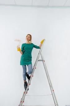 Uma jovem em uma escada pinta uma parede branca com um rolo. reparação do interior.