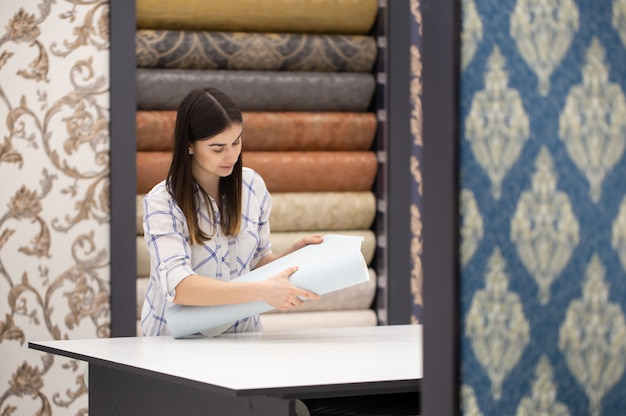 Uma jovem em uma loja escolhe papel de parede para sua casa. c