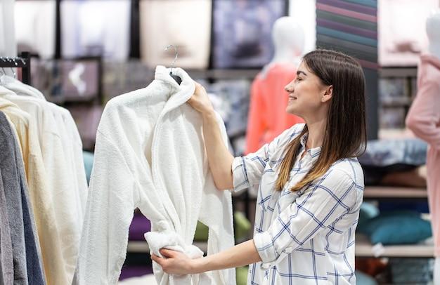 Uma jovem em uma loja escolhe tecidos. o conceito de comprar uma casa.