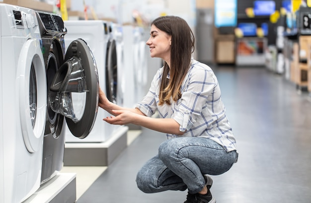 Uma jovem em uma loja escolhe uma máquina de lavar.