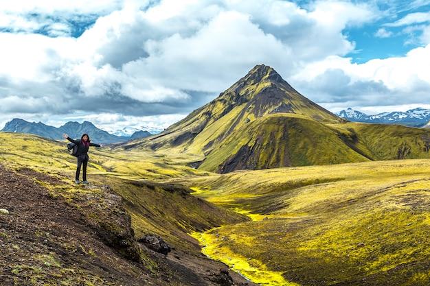 Uma jovem em uma montanha verde e um belo rio de musgo na caminhada de 54 km de landmannalaugar, islândia