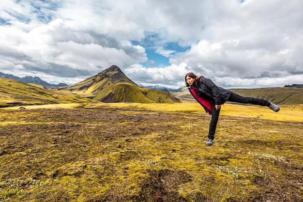 Uma jovem em uma montanha verde na caminhada de 54 km de landmannalaugar, islândia