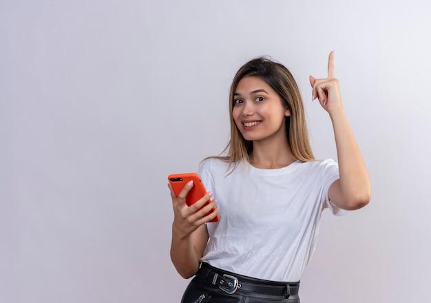 Uma jovem empolgada em uma camiseta branca finalmente entendendo algo e tendo uma ótima ideia e levantando o dedo em um gesto de eureka