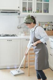 Uma jovem empregada limpando a casa com um esfregão há uma cozinha ao fundo