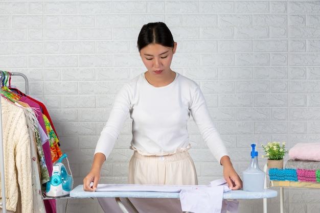 Uma jovem empregada que está preparando uma camisa na tábua de passar roupas com um tijolo branco.