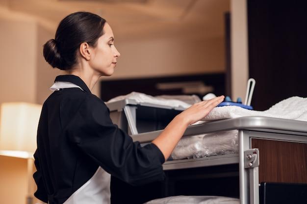 Uma jovem empregada uniformizada recebendo algumas toalhas limpas