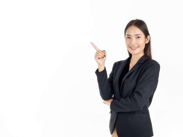 Uma jovem empresária asiática atraente em um terno preto apontando o dedo para apresentar no espaço da cópia e olhando a câmera com um sorriso dentuço