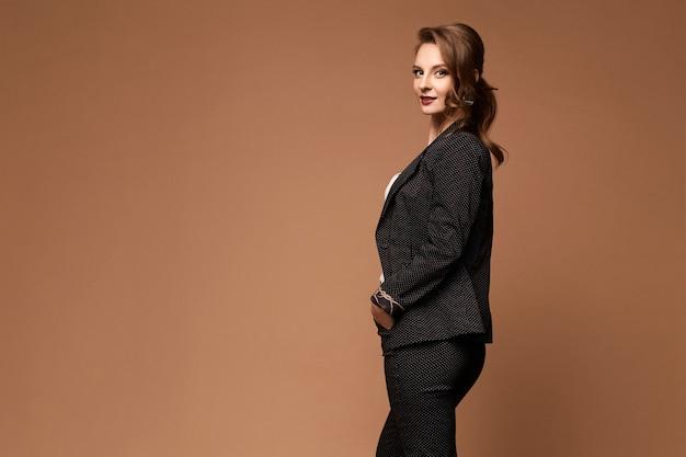 Uma jovem empresária em um terno estiloso posa sobre uma superfície bege, isolada com um espaço de cópia à esquerda