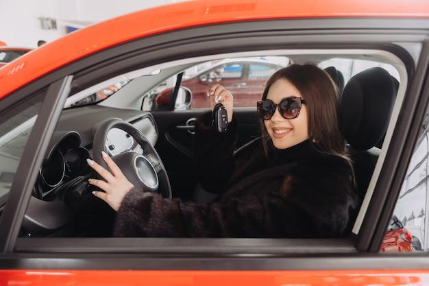 Uma jovem empresária está testando carros em uma loja de carros