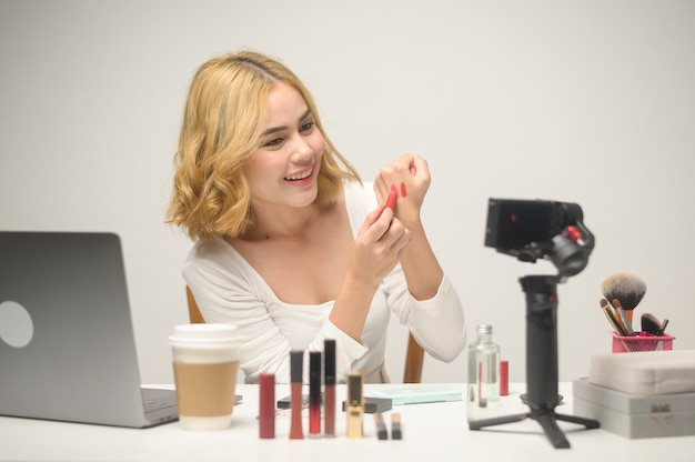 Uma jovem empresária loira trabalhando com laptop apresenta produtos cosméticos durante a transmissão ao vivo on-line sobre o estúdio de fundo branco, vendendo on-line e o conceito de blogueira de beleza