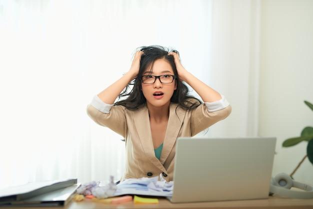 Uma jovem empresária parece estressada enquanto trabalha no computador. tiro horizontal.