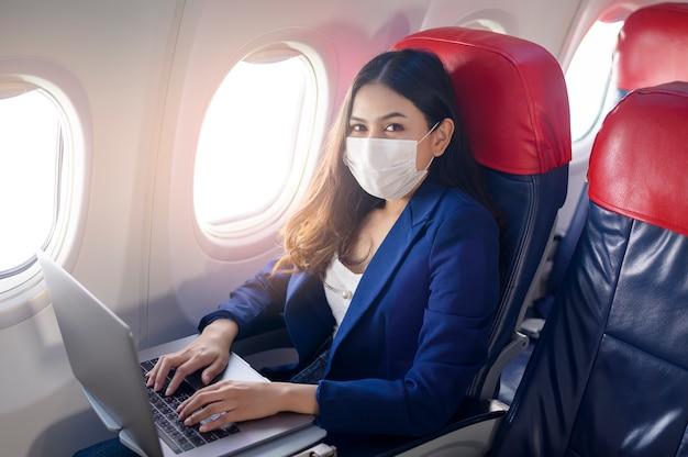 Uma jovem empresária usando máscara facial está usando um laptop a bordo. nova viagem normal após o conceito de pandemia covid-19