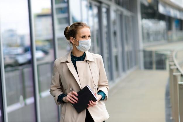 Uma jovem empresária vestindo uma máscara de saúde e falando ao telefone na cidade