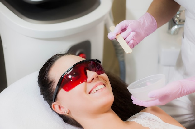 Uma jovem encontra-se no consultório de um cosmetologista em um procedimento de depilação a laser.