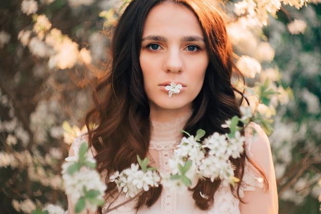 Uma jovem encostada na superfície de árvores floridas