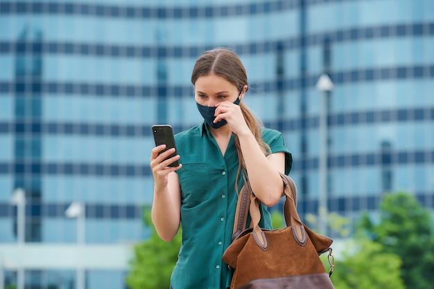 Uma jovem endireita sua máscara médica azul marinho para evitar a disseminação do coronavírus