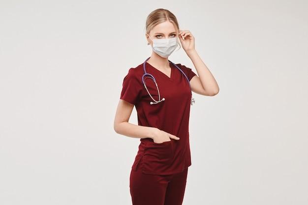 Uma jovem enfermeira com um uniforme médico e cobertura protetora para o rosto, isolado no branco
