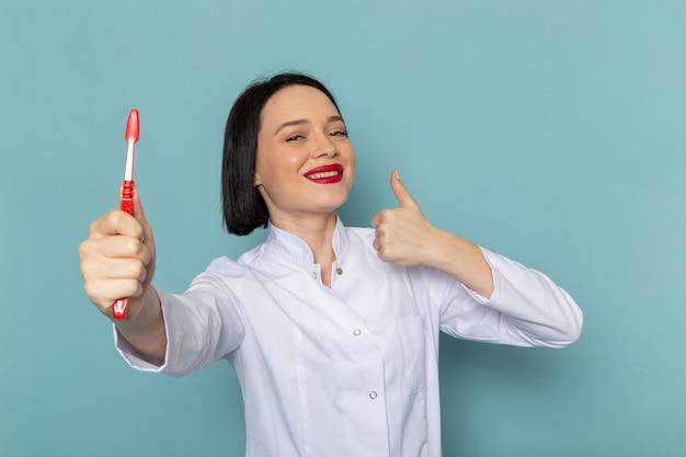Uma jovem enfermeira com vista frontal em um terno médico branco e um estetoscópio azul segurando uma escova de dentes na mesa azul.