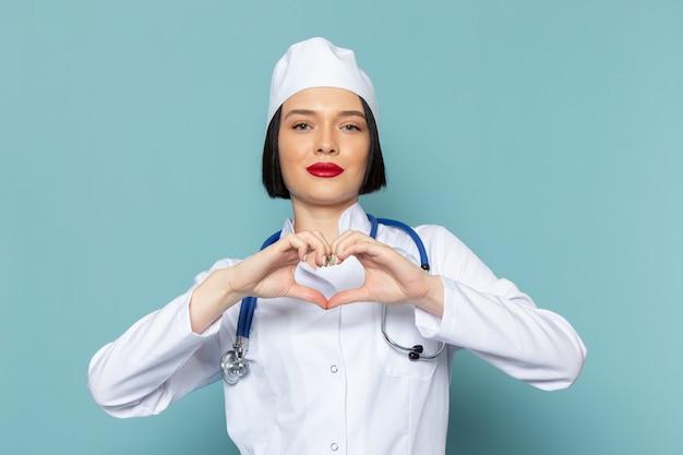 Uma jovem enfermeira com vista frontal, vestindo um terno médico branco e um estetoscópio azul, mostrando o sinal do coração na mesa azul.