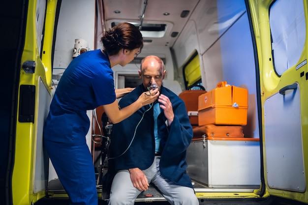 Uma jovem enfermeira de uniforme entrega uma máscara de oxigênio a um homem resgatado do fogo