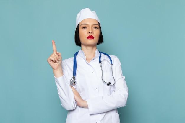 Uma jovem enfermeira de vista frontal em um terno médico branco e um estetoscópio azul posando com o dedo levantado na mesa azul.