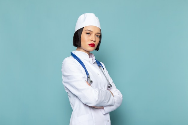 Uma jovem enfermeira de vista frontal em um terno médico branco e um estetoscópio azul posando sobre a mesa azul.