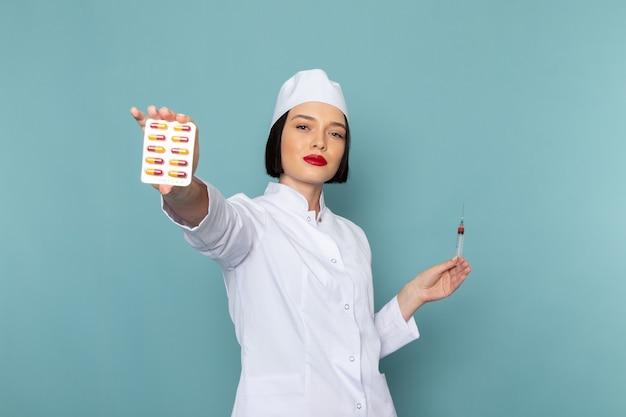 Uma jovem enfermeira em um terno branco segurando comprimidos na mesa azul.