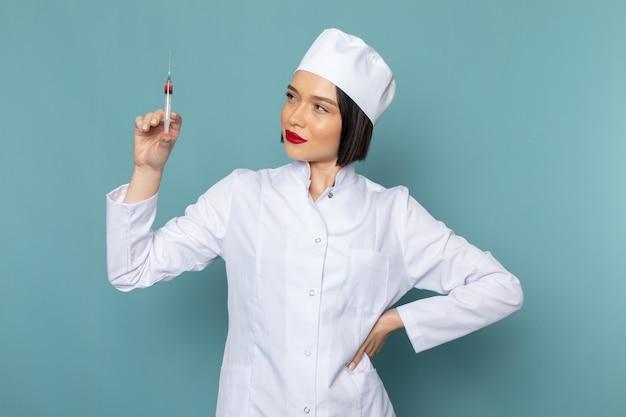 Uma jovem enfermeira em um terno branco segurando uma injeção na mesa azul.