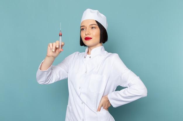 Uma jovem enfermeira feminina em um terno branco preparando a injeção na mesa azul.