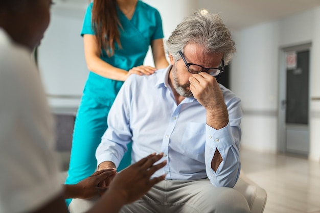 Uma jovem enfermeira ou cuidadora gentil e atenciosa, ajudando um homem aposentado mais velho a falar, dando conforto