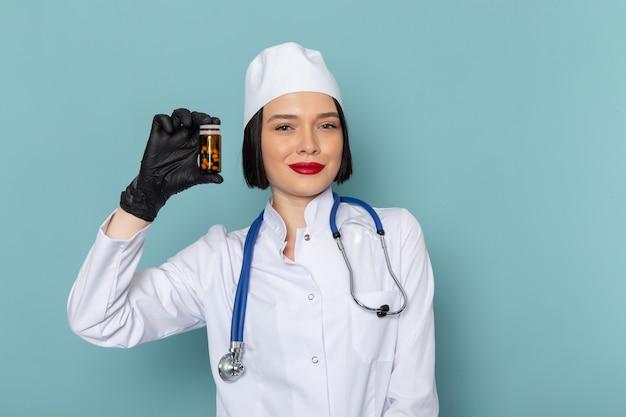 Uma jovem enfermeira, vista frontal, em um terno médico branco e um estetoscópio azul segurando comprimidos na mesa azul.